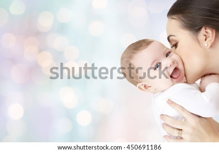 family, motherhood, parenting, people and child care concept - happy mother kissing adorable baby over blue holidays lights background #450691186