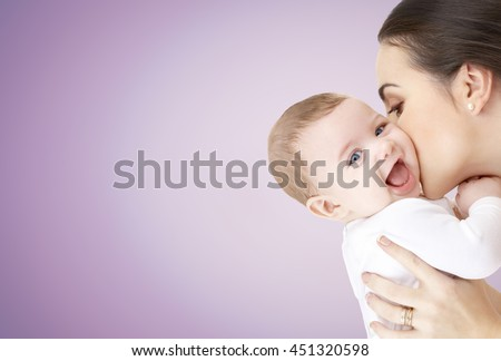 family, motherhood, parenting, people and child care concept - happy mother kissing adorable baby over violet background