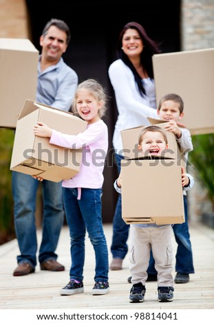 Family moving home and carrying cardboard boxes outdoors