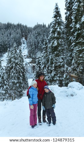 Family near alps mountain waterfall Krimml (Austria, Tirol). Winter view.