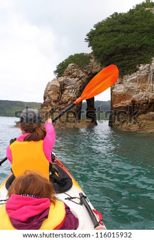 Family ocean kayaking among limestone cliffs in a beautiful Abel Tasman National Park in New Zealand