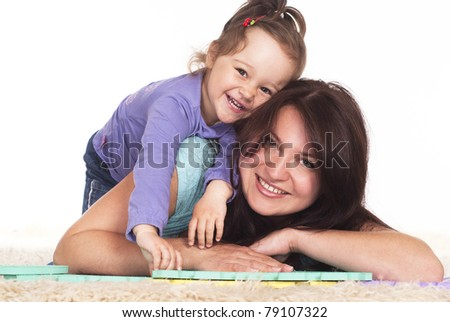 family of a two playing on carpet - stock photo