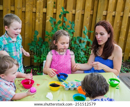 Family of children painting and decorating eggs outside.  Mother and kids have fun as they paint their color dyed Easter eggs during the spring season in a beautiful garden setting.  Part of a series.