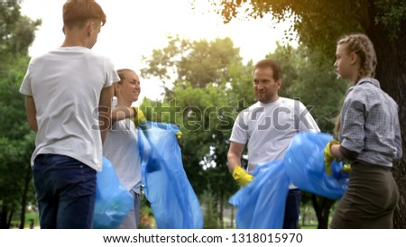 Family of enthusiasts doing voluntary Saturday work, picking garbage in park
