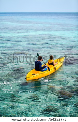 Family of father and daughter paddling on colorful yellow kayaks at tropical ocean water during summer vacation