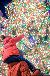 Family of father and kid on the background of the Rockefeller Christmas tree in New York. Beautiful Christmas Tree at Rockefeller center