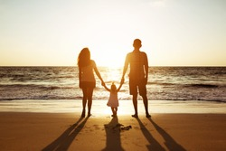 Family of father mother and daughter stands on background of sunset sea. Three silhouettes of happy people