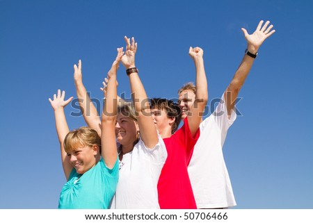 family of four arms open over blue sky background