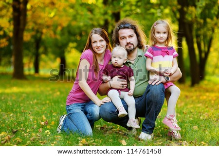 Family of four at beautiful autumn day - stock photo