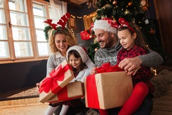 Family of four celebrating Christmas, exchanging presents