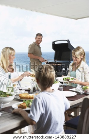 Family of four enjoying barbecue against the sea