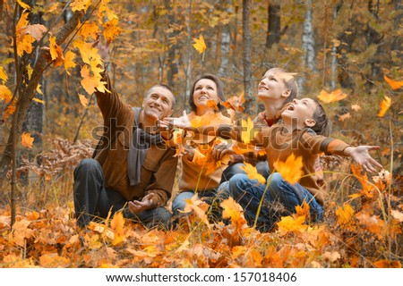 Family of four enjoying golden leaves in autumn park