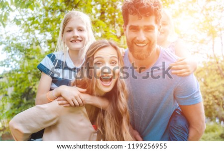 Family of four having fun, daddy and mommy are carrying the kids piggyback #1199256955