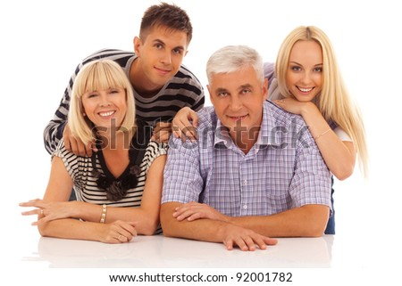 family of four in front of the white table portrait isolated on white background