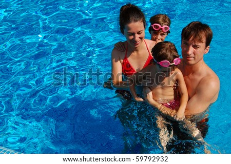 Family of four in swimming pool