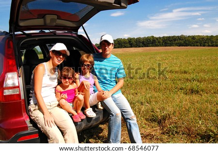 Family of four near their car on vacation
