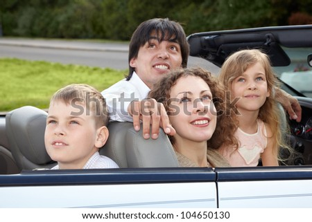 Family of four - parents and son with daughter -  sits in a cabriolet and looks on the sky.