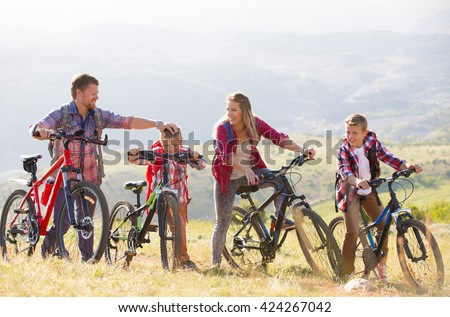Family of four people riding bikes in the mountains