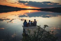 family of four people sitting on the shore on a wooden bridge of a large lake in summer and watching the beautiful sunset with dog back view