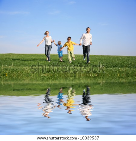 family of four running grass sky water