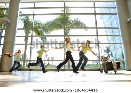 Family of four running through the airport in line with the father pushing luggage trolley in the front and smiling ストックフォト ©