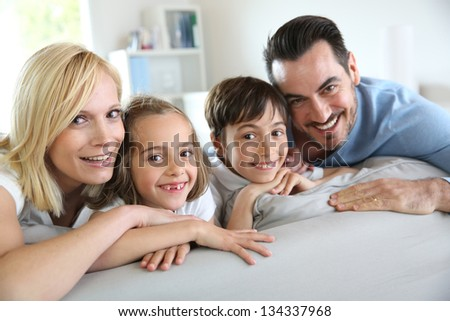 Family of four sitting in sofa at home #134337968