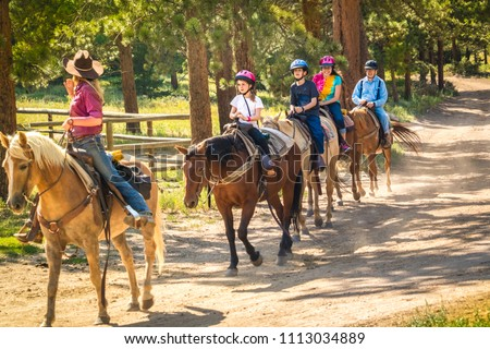 Family of four - two children, their mother and grandfather -- taking a horseback riding  lesson in the woods in the Rocky Mountain, Colorado, USA;