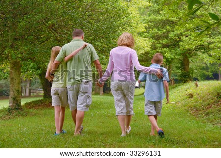 family of four walking in the grass holding hands