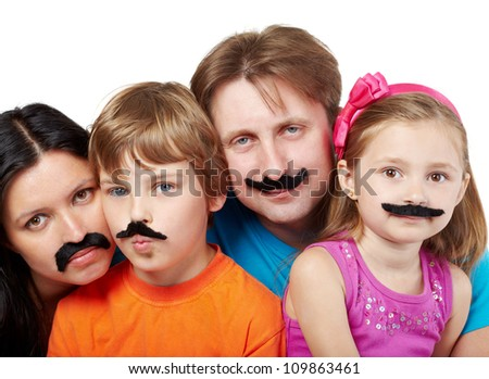 Family of four with glued artificial mustaches, mother and son are serious, father and daughter smile.