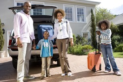 Family of four with suitcases by back of car, smiling, portrait, low angle view