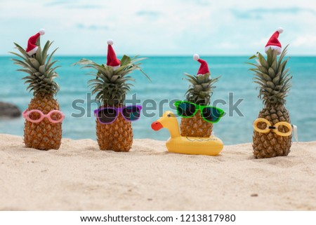 baded4e6 Family of funny attractive pineapples in stylish sunglasses on the sand  against turquoise sea. Wearing