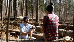 family of lumberjacks. A man kneels in front of a woman in the forest. Woman lumberjack