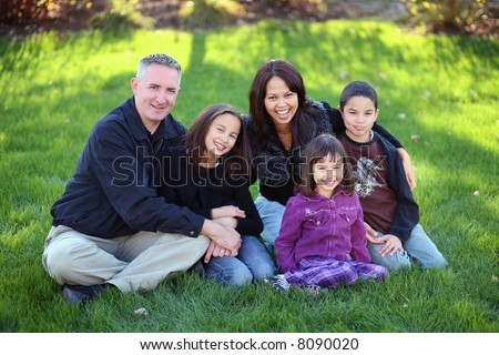 Family of 5 made of diverse nationalities outdoors