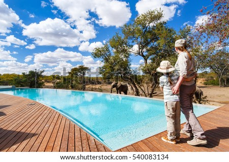 Family of mother and child on African safari vacation enjoying wildlife viewing standing near swimming pool