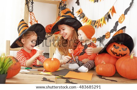 family of mother and children decorate the home for Halloween