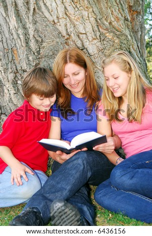 Family of mother and children reading a book under a tree in summer park