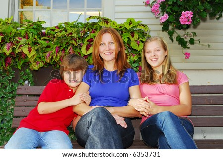 Family of mother and children sitting in front of their house