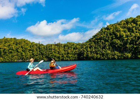 Family of mother and son paddling on colorful kayak at mangroves during summer vacation