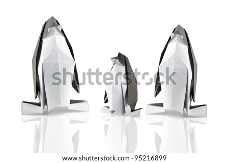 family of origami penguins on the white reflection background
