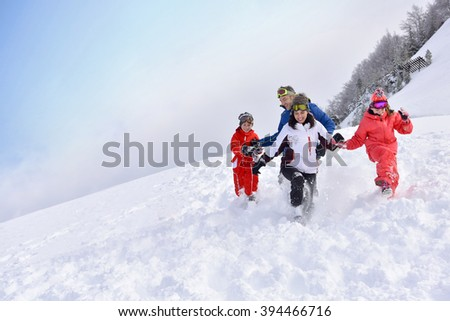 Family of 4 running down in snowy slope
