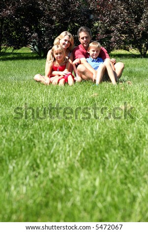 family of 4 sitting outside in grass