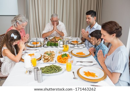Family of six saying grace before meal at dining table in the house
