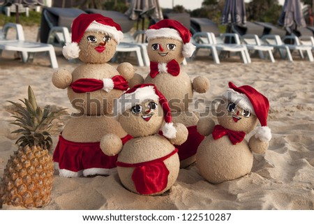 Family of snowmen on the beach in xmas outfits with smiling faces