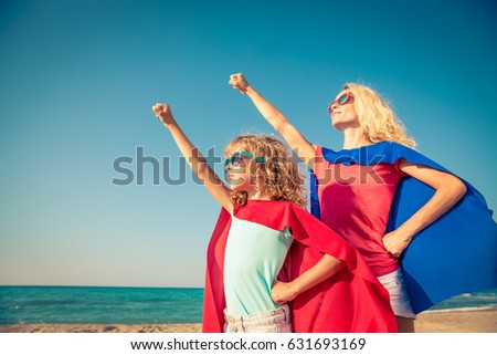 Family of superheroes on the beach. Mother and daughter having fun outdoor. Summer vacation concept #631693169