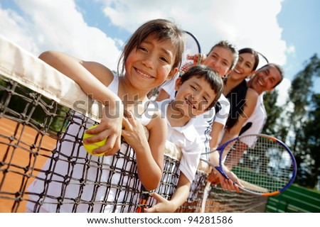 Family of tennis players at the court next to the net