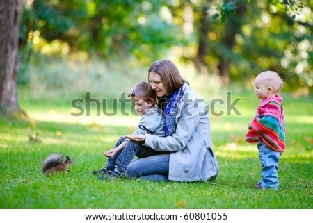 Family of three and little squirrel in autumn park