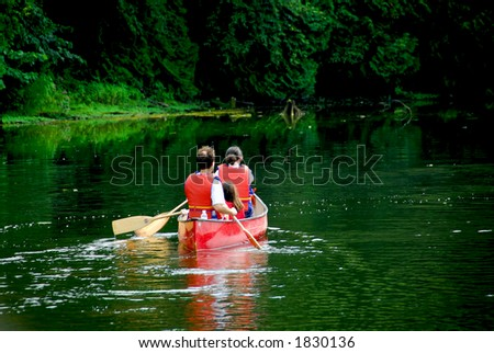 Family of three canoing on a calm green river