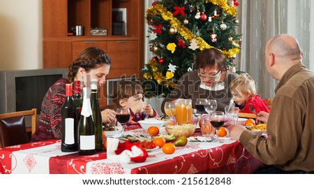 family of three generations  celebrating Christmas  over holiday table at home interior #215612848