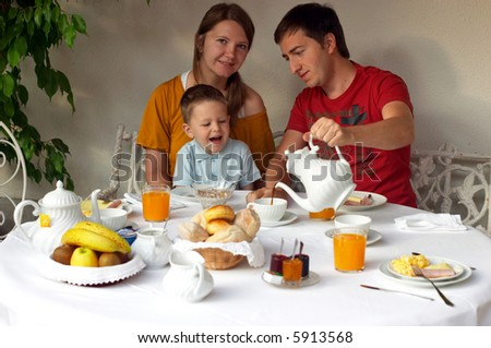 Family of three having breakfast at terrace of theirs house