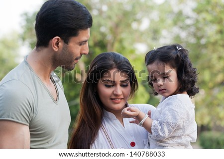 ShutterStock family of three in outdoor young couple with daughter in ...